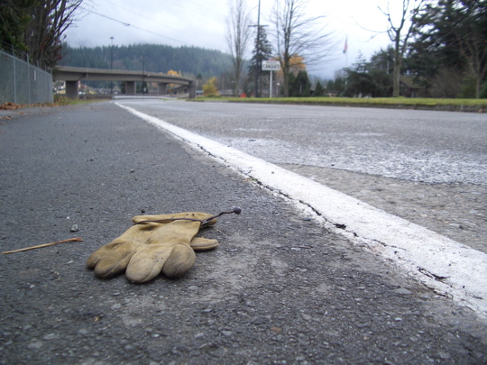 foreground: leather work glove, background: receding roadway, flyover freeway ramp, forested hillside