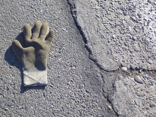 rubberized work glove on paved shoulder alongside cracked concrete road surface