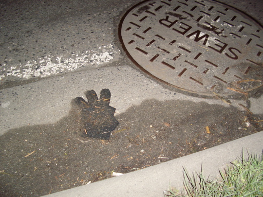 glove in the gutter near a man hole cover