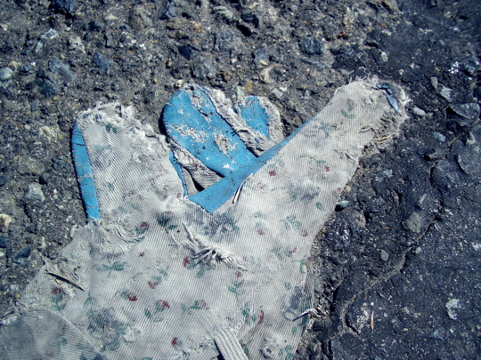 flattened, tattered, and worn garden glove on pavement