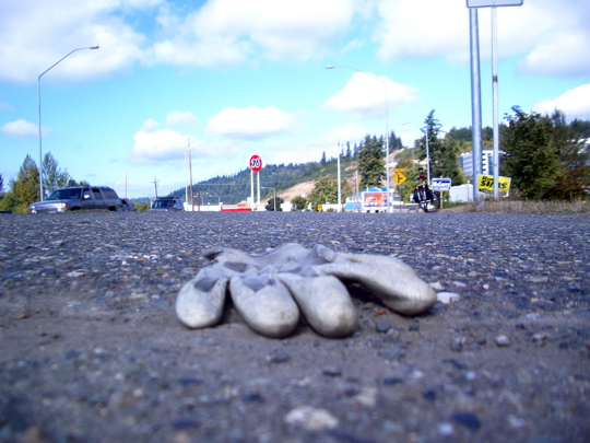 white knit rubberized glove on pavement with cars and sky in background