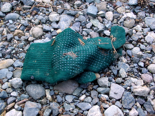 green glove with gripper dots on grey gravel