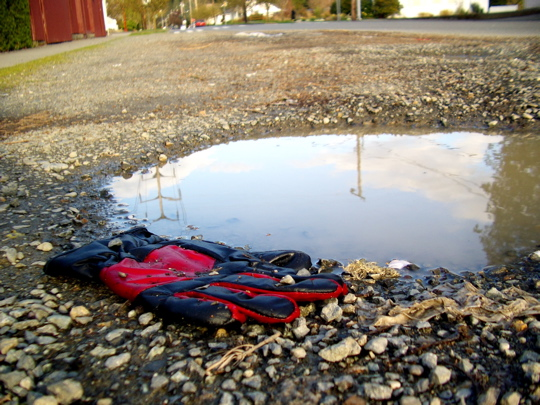 red and black glove near a puddle with reflection of sky and power lines