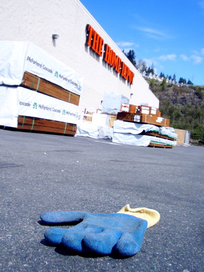 blue rubberized glove in parking lot outside Home Depot