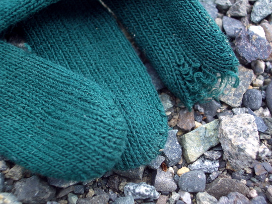 green knit glove with an unravelling finger on gravel