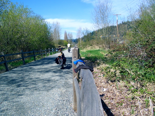 two gloves on a fence rail, a parked xtracycle, and a cyclist