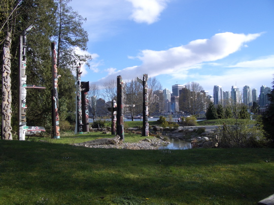totem poles against Vancouver, BC skyline
