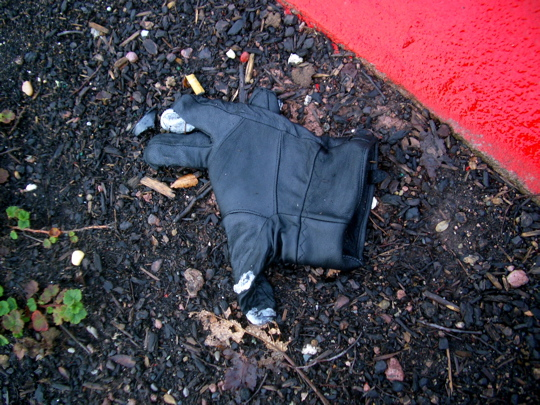 tattered black glove by a red curb