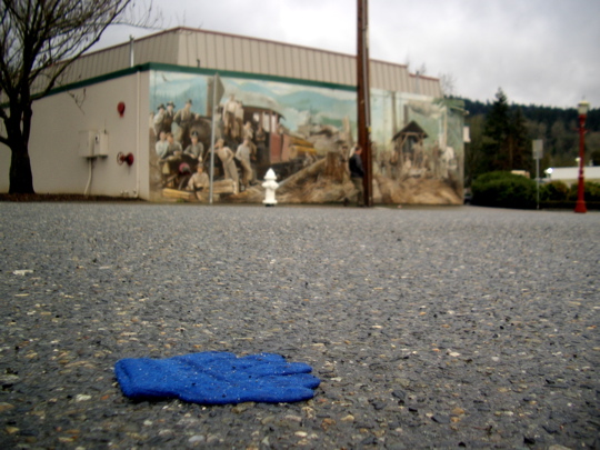 blue glove in street with mural in background