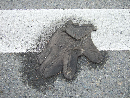 leather glove on a road stripe in a halo of sand